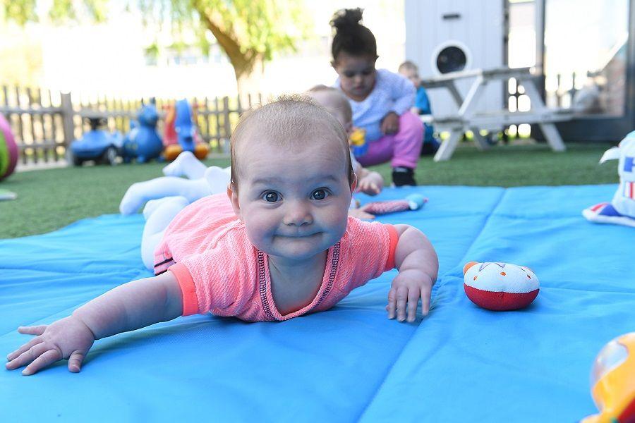Baby speelt buiten op het kinderdagverblijf