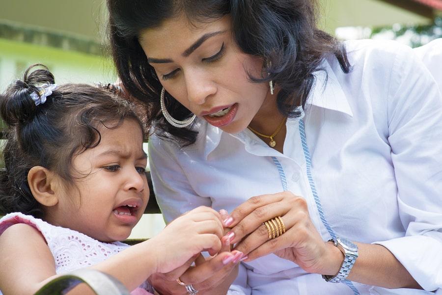 Moeder bekijkt een wespensteek bij haar kind