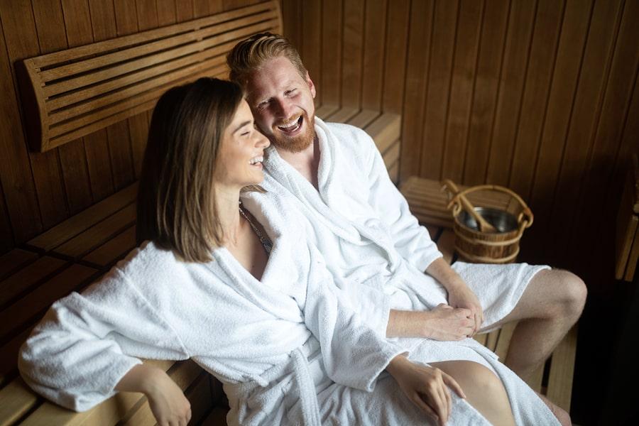 Zwangere vrouw zit met haar partner in de sauna