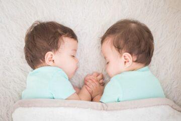 Eeneiige tweelingbroertjes liggen hand in hand te slapen.