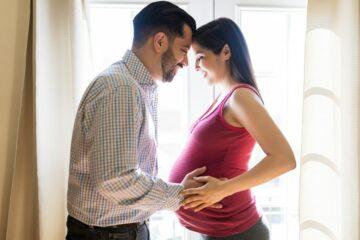 Man voelt aan de buik van zijn zwangere vrouw die is gevuld met vruchtwater