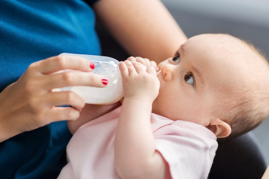 Baby drinkt flesvoeding uit een flesje