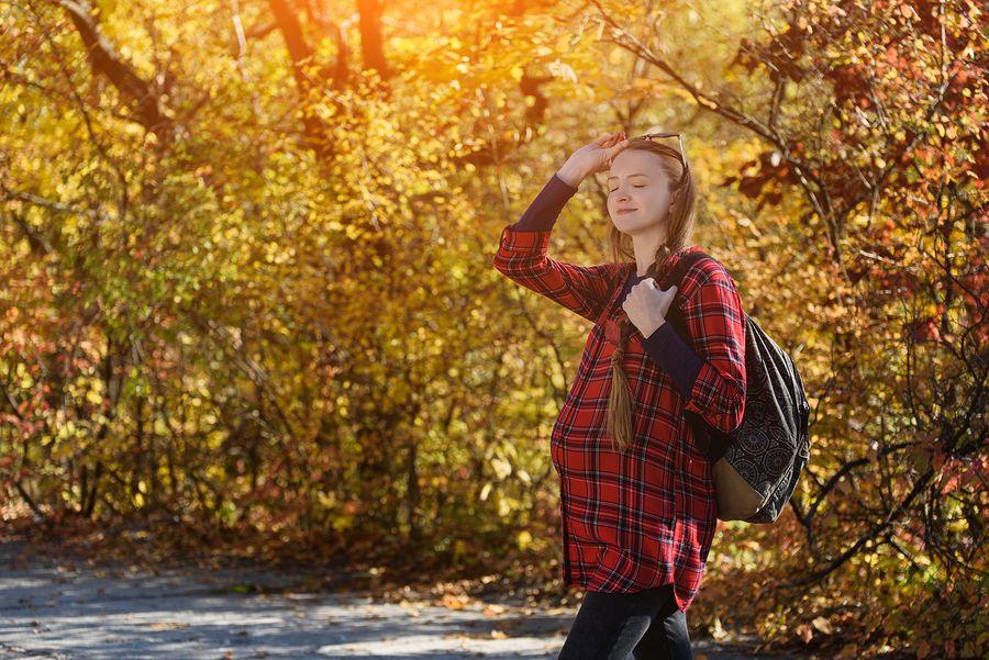 Vrouw draagt winterse zwangerschapskleding in het bos