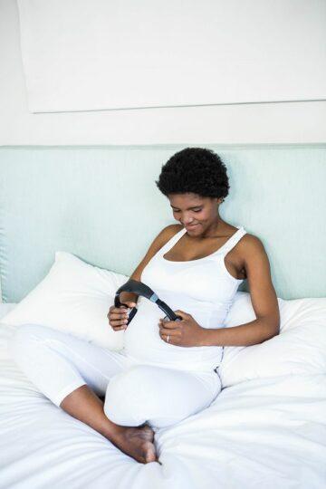 Zwangere vrouw zit op bed met koptelefoon op de buik
