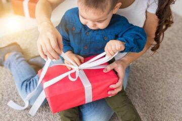 Jongetje pakt sinterklaascadeaus uit op schoot bij moeder