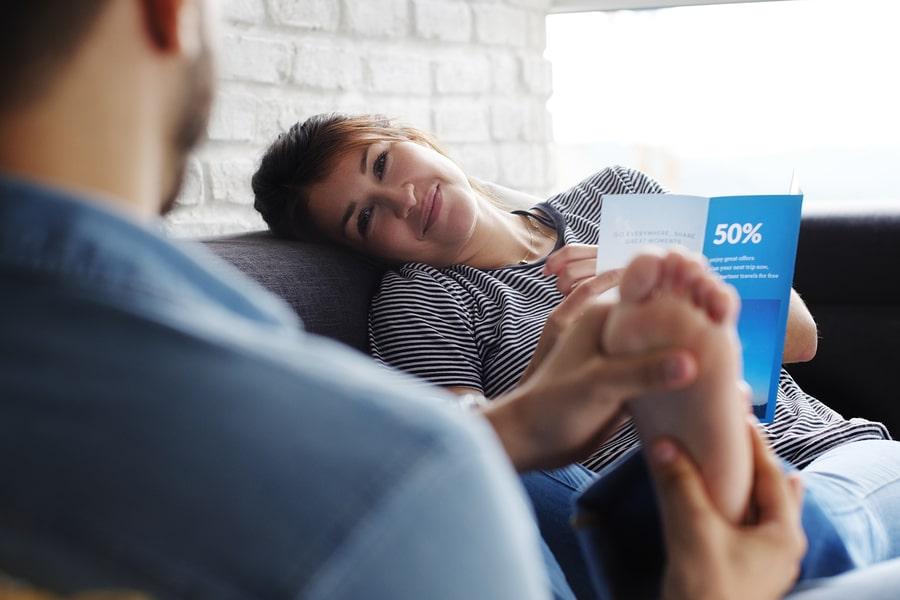 Zwangere vrouw krijgt voetmassage van haar partner want ze heeft last van vocht vasthouden