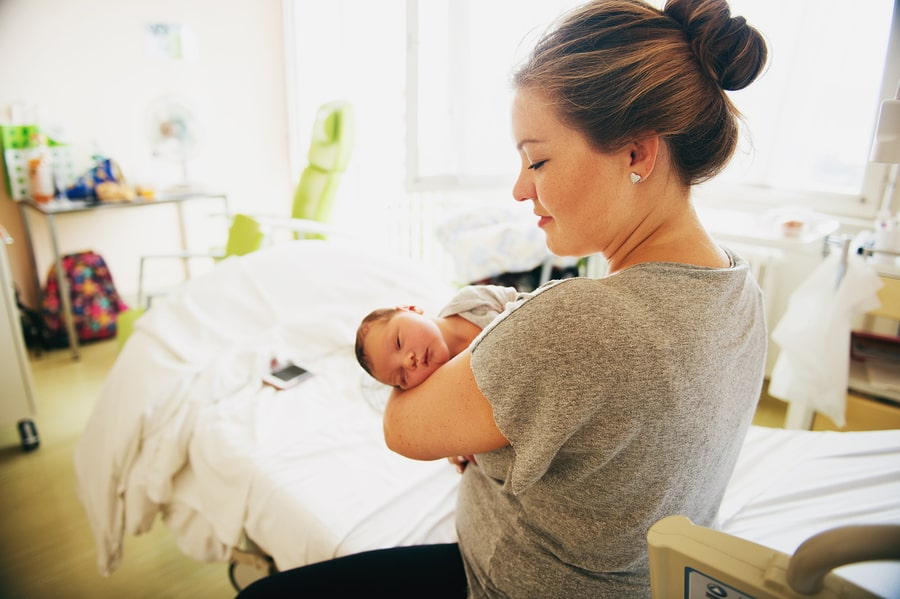 Vrouw met baby in haar armen in bevallen in een geboortehuis