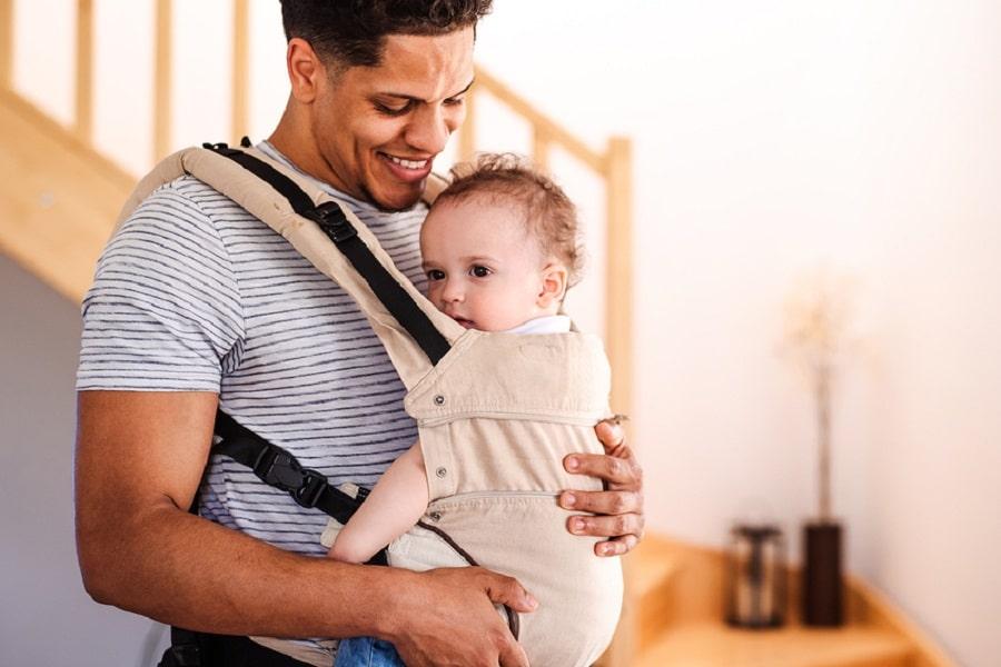 Vader kijkt liefdevol naar zijn baby in de draagzak