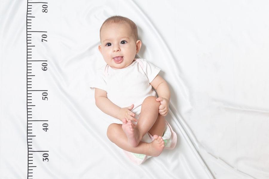 Baby ligt naast meetlint om de lengte te berekenen als je wil weten hoe lang wordt mijn kind