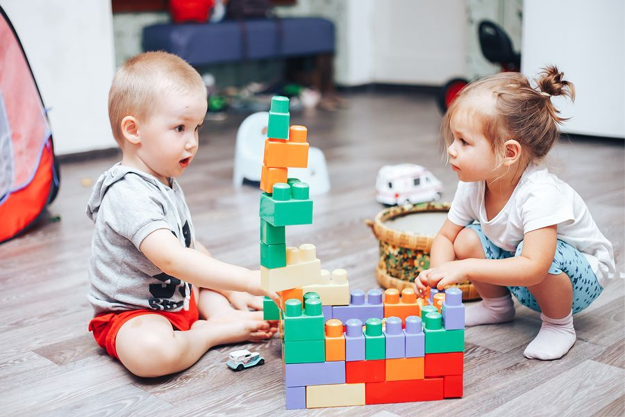 Jongen en meisje bouwen toren van blokken
