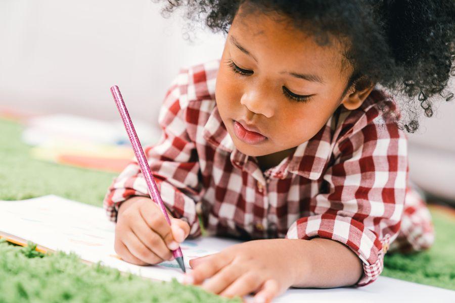 Jong meisje kleurt bij het kinderdagverblijf
