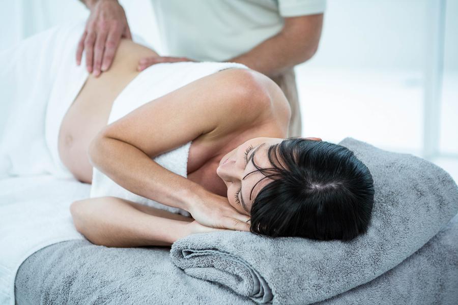 Zwangere vrouw krijgt zwangerschapsmassage op massagetafel