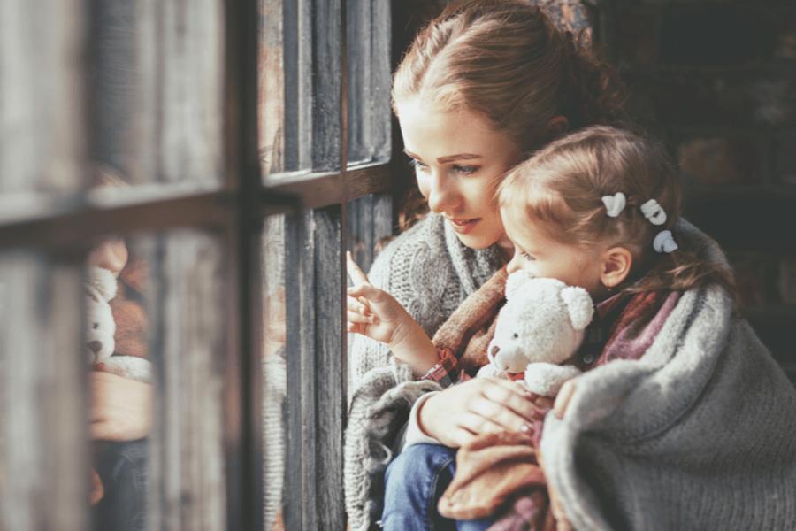 Kind dat bang is voor onweer kijkt samen met moeder uit het raam