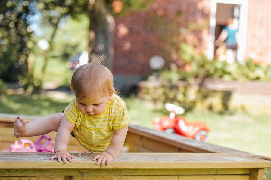 Kind speelt in zandbak bij kinderdagverblijf