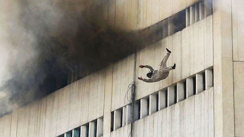 A man falls from a high floor of a burning building in central Lahore