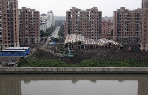 A 13-storey apartment building lies on its side after toppling and burying one worker on Saturday, in Shanghai