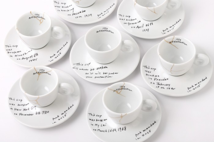 This image released by Illy North America shows a collection of espresso cups and saucers called, Yoko Ono: Mended Cups - illy Art Collection, featuring the dates and places of six tragic events written in Ono's handwriting. The collection is inspired by Kintsugi, the Japanese technique of repairing cracked pottery with brushstrokes of gold. The line for illy Art Collection is being released alongside Ono's upcoming show at the Museum of Modern Art. (Lou Manna/Illy North America via AP)