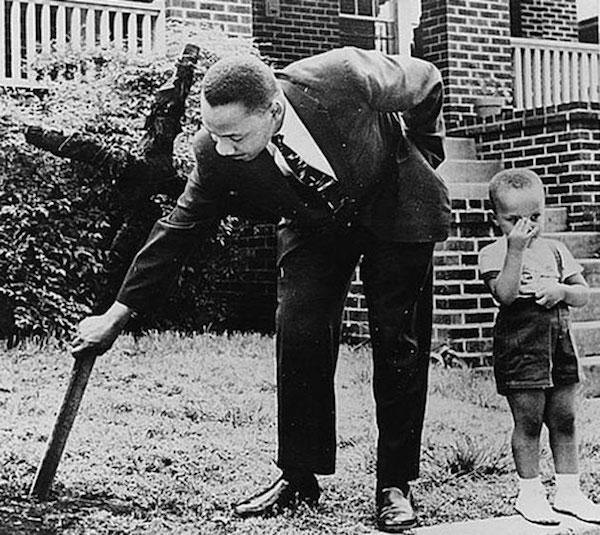 Martin Luther King Jr. junto a su hijo arranca una cruz quemada en el patio de su casa, 1960