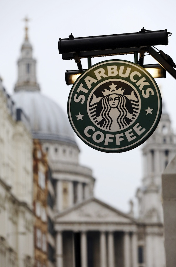St Paul's Cathedral is pictured behind a signage for a Starbucks coffee shop in London October 8, 2012. Picture taken October 8, 2012.   To match Special Report BRITAIN-STARBUCKS/TAX      REUTERS/Luke Macgregor (BRITAIN - Tags: BUSINESS RELIGION LOGO) - RTR395SX
