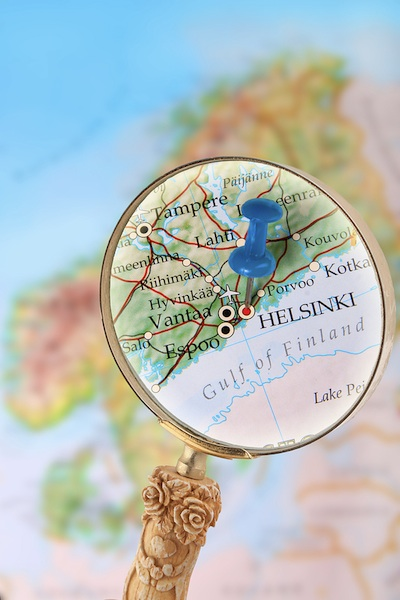 Blue tack on map of Scandinavia with magnifying glass looking in on Helsinki Finland