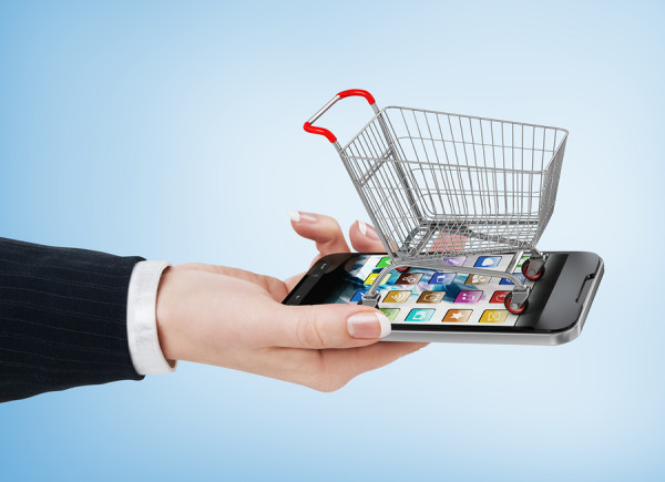 Woman hand holding smartphone with shopping cart. E-commerce concept.