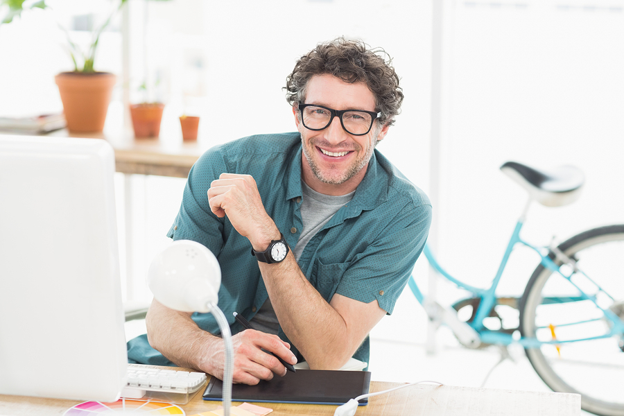 Cheerful graphic designer using a graphics tablet in a modern of