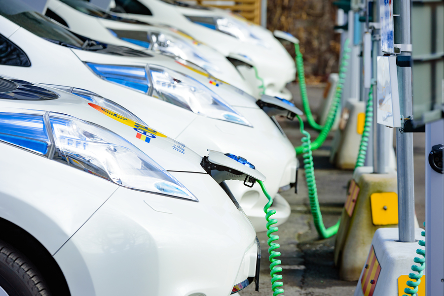 Kristianstad Sweden - March 20 2016: The charging of some white Nissan electrical cars. Green coiled cables are attached to the front of the cars. These are C4 Energi carpool rentals.