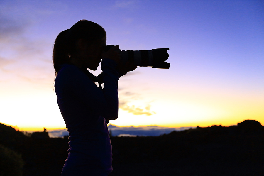 Photographer taking pictures with SLR camera at night. Nature landscape photographer with telephoto lens. Silhouette of woman taking photo after sunset.
