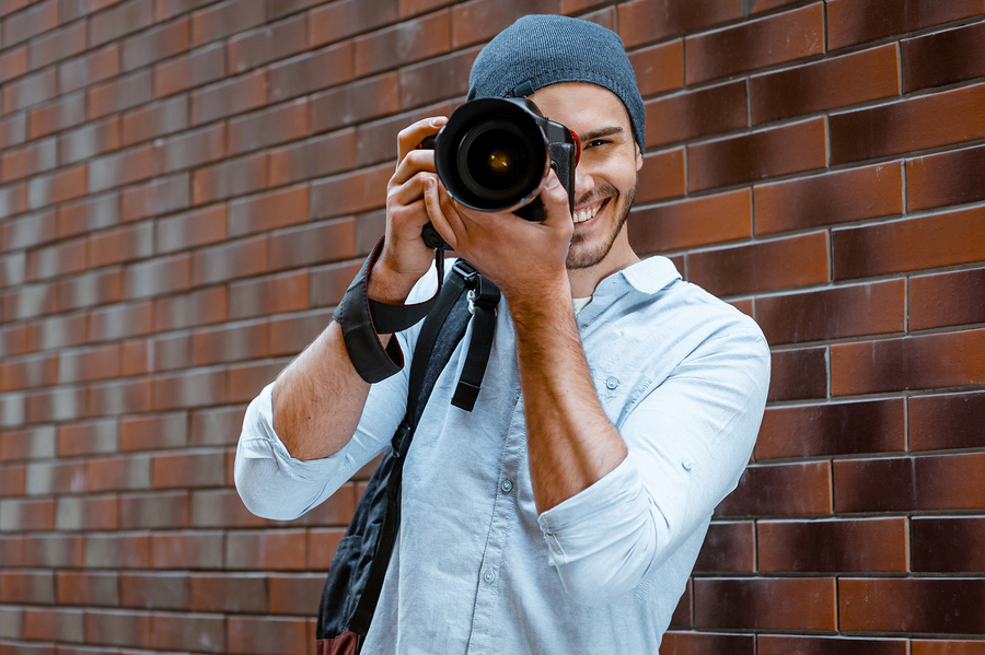 Portrait of stylish handsome young photographer with bristle standing outdoors and leaning on brick wall. Young man wearing shirt and hat. Man with professional camera looking through lens