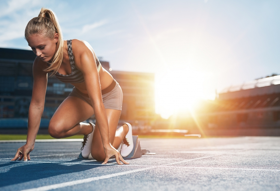 Young woman athlete at starting position ready to start a race. Female sprinter ready for sports exercise on racetrack with sun flare.