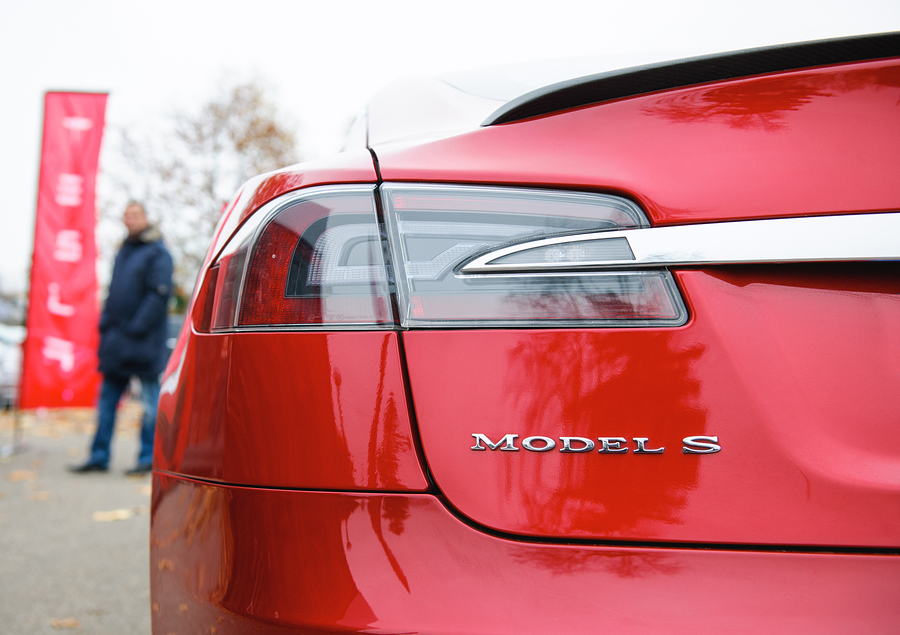 PARIS FRANCE - NOVEMBER 29, 2014: Tesla Model S signage of a red car outside the dealership house with male silhouette admiring the car. Tesla is an American company that designs manufactures and sells electric cars