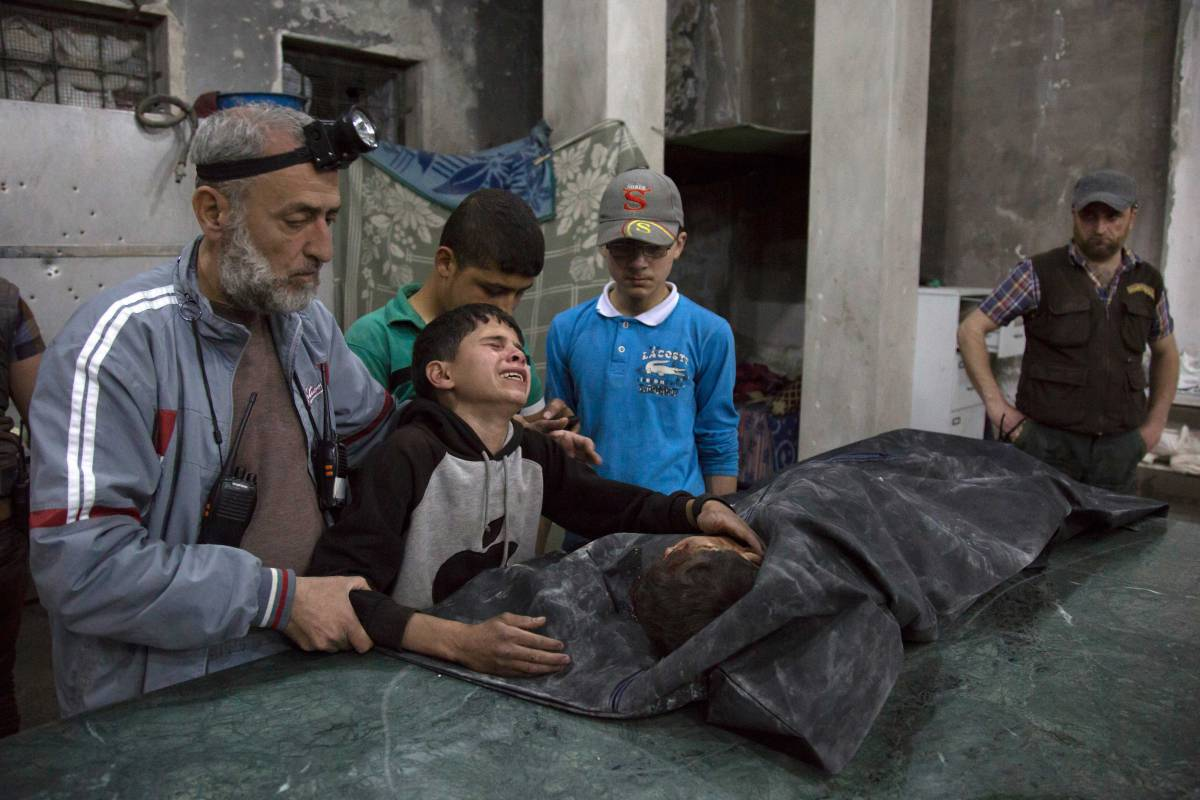 A Syrian boy is comforted as he cries next to the body of a relative who died in a reported airstrike on April 27, 2016 in the rebel-held neighbourhood of al-Soukour in the northern city of Aleppo. / AFP / KARAM AL-MASRI (Photo credit should read KARAM AL-MASRI/AFP/Getty Images)
