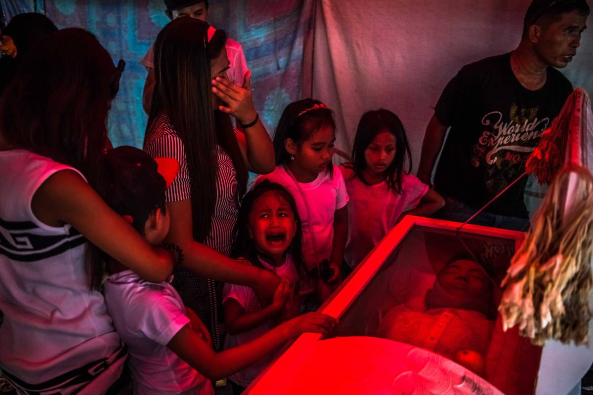 """Jimji, 6, cries out in anguish, saying """"Papa"""" as workers move the body of her father, Jimboy Bolasa, 25, for burial, in Manila, Philippines, Oct. 9, 2016. Bolasa was found murdered along with his neighbor. A bloody and chaotic campaign against drugs that President Rodrigo Duterte began when he took office on June 30 has seen about 2,000 people slain at the hands of the police alone. (Daniel Berehulak/The New York Times)"""