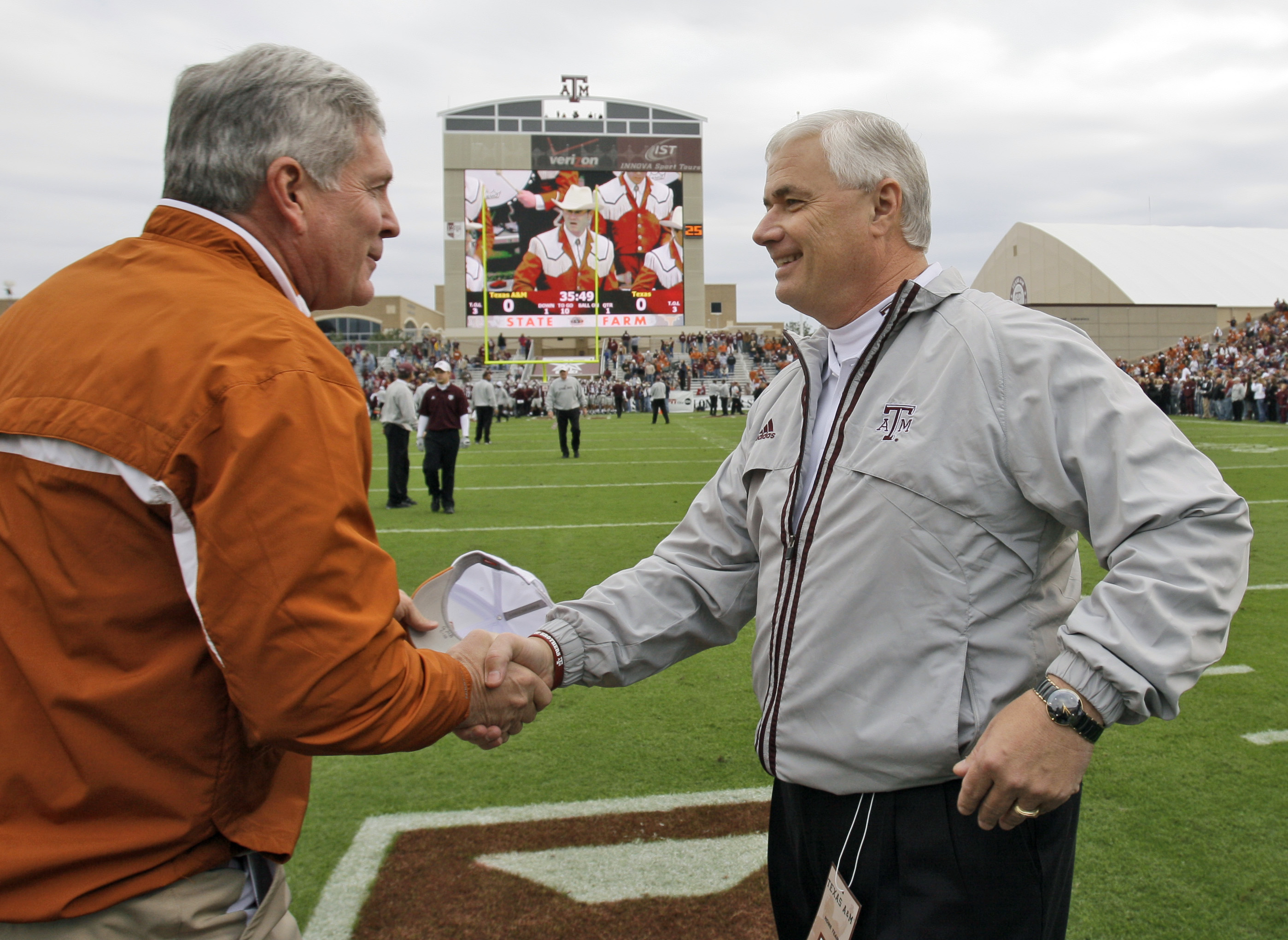 Texas coach Mack Brown, left, shakes hands with Texas A&M coach Dennis Franchione before a football game Friday, Nov. 23, 2007, in College Station, Texas. (AP Photo/David J. Phillip)