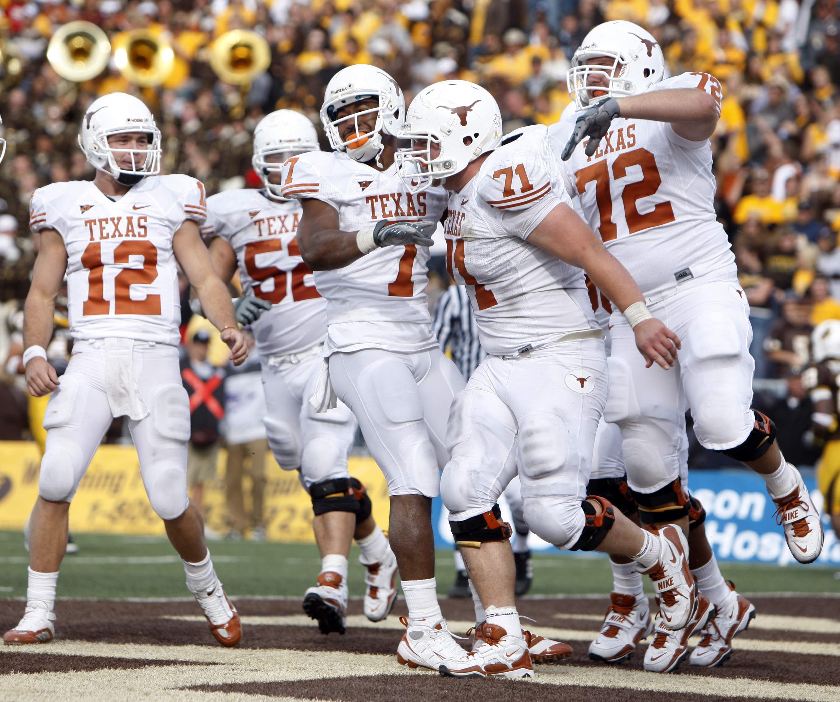 Texas wide receiver John Chiles, third from left, is congratulated after taking a pass in for a touchdown by quarterback Colt McCoy, left, Chris Hall, second from right, and offensive tackle Britt Mitchell during the fourth quarter of Texas' 41-10 victory over Wyoming in an NCAA college football game in Laramie, Wyo., on Saturday, Sept. 12, 2009. (AP Photo/David Zalubowski)