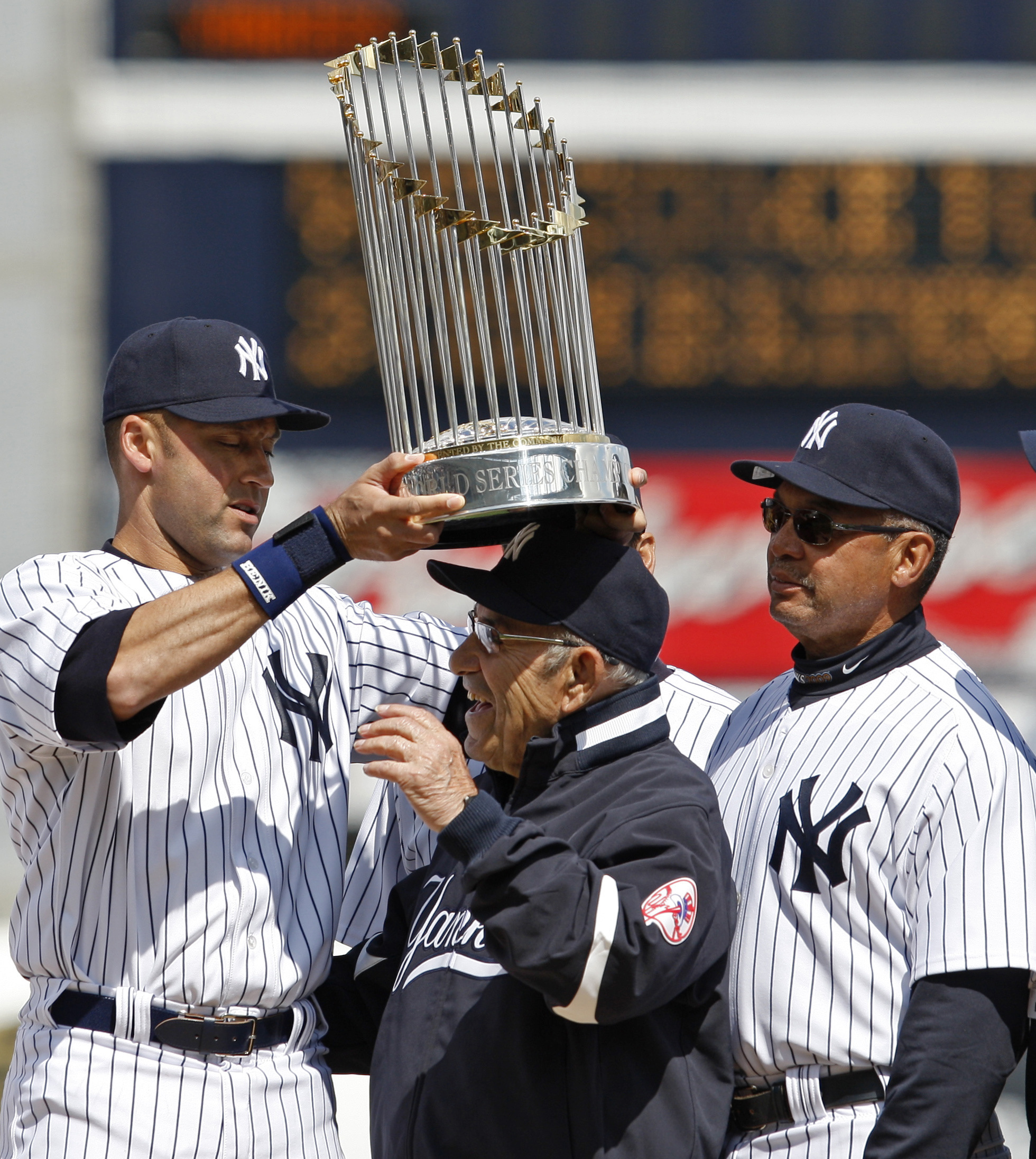 New York Yankees captain Derek Jeter, left, balances the 2009 World Series trophy atop Yogi Berra's head as Hall of Famer Reggie Jackson watches during pregame ceremonies prior to the during Yankees home opener spring training baseball game against the Pittsburgh Pirates at Steinbrenner Field in Tampa, Fla., Wednesday, March 3, 2010. (AP Photo/Kathy Willens)