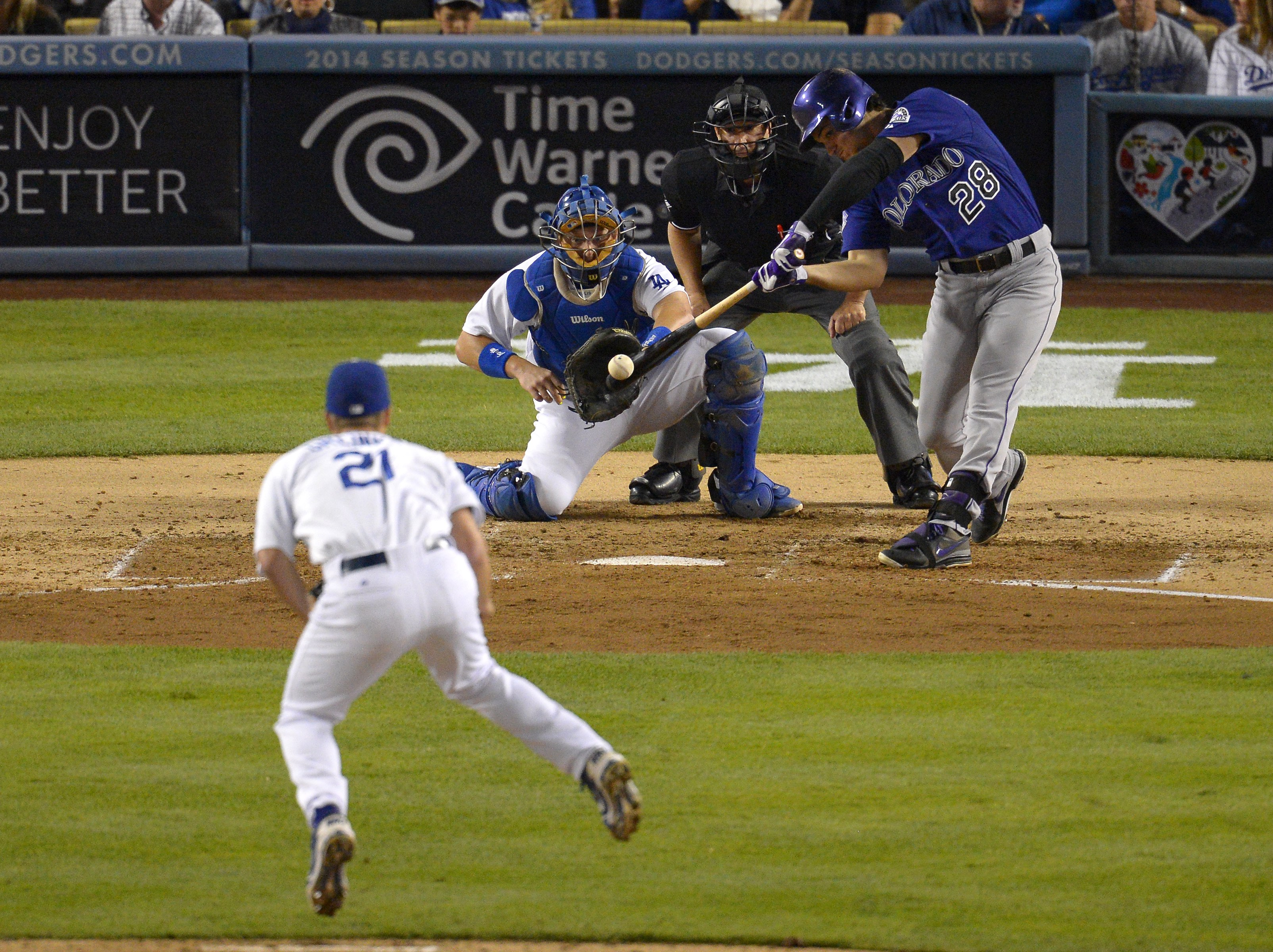 Colorado Rockies' Nolan Arenado, right, hits an RBI double as Los Angeles Dodgers starting pitcher Zack Greinke, left, and catcher A.J. Ellis look on along with home plate umpire Jim Reynolds during the fourth inning of their baseball game, Saturday, Sept. 28, 2013, in Los Angeles. (AP Photo/Mark J. Terrill)