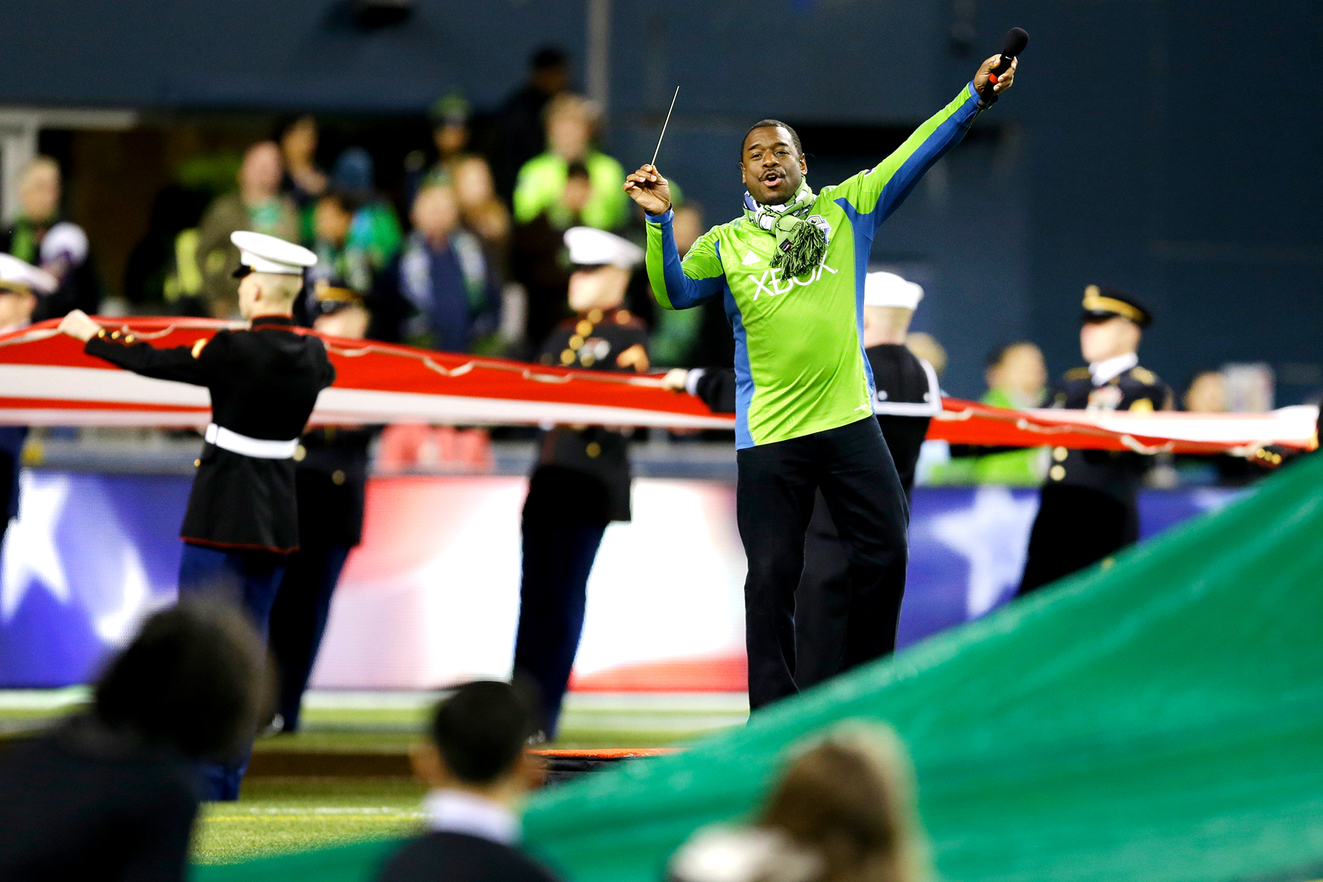 Stephen Michael Newby leads the crowd in the singing of the national anthem before the first game of the Western Conference semifinals between the Seattle Sounders and the Portland Timbers in the MLS Cup soccer playoffs, Saturday, Nov. 2, 2013, in Seattle. (AP Photo/Ted S. Warren)