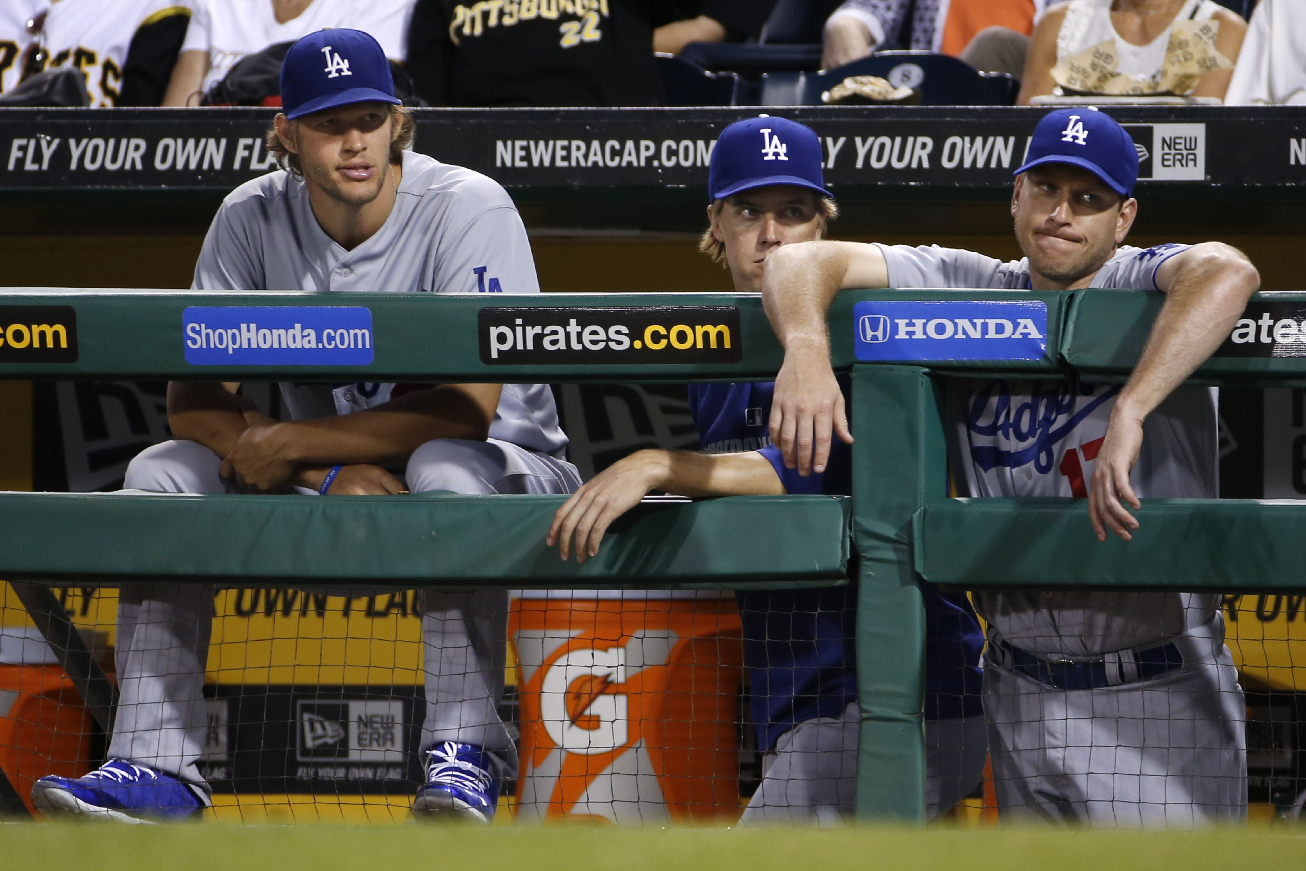 Los Angeles Dodgers starting pitchers Clayton Kershaw, left, and Zack Greinke, center, and catcher A.J. Ellis watch from the dugout during the ninth inning of a 6-1 loss to the Pittsburgh Pirates in a baseball game in Pittsburgh Wednesday, July 23, 2014. (AP Photo)