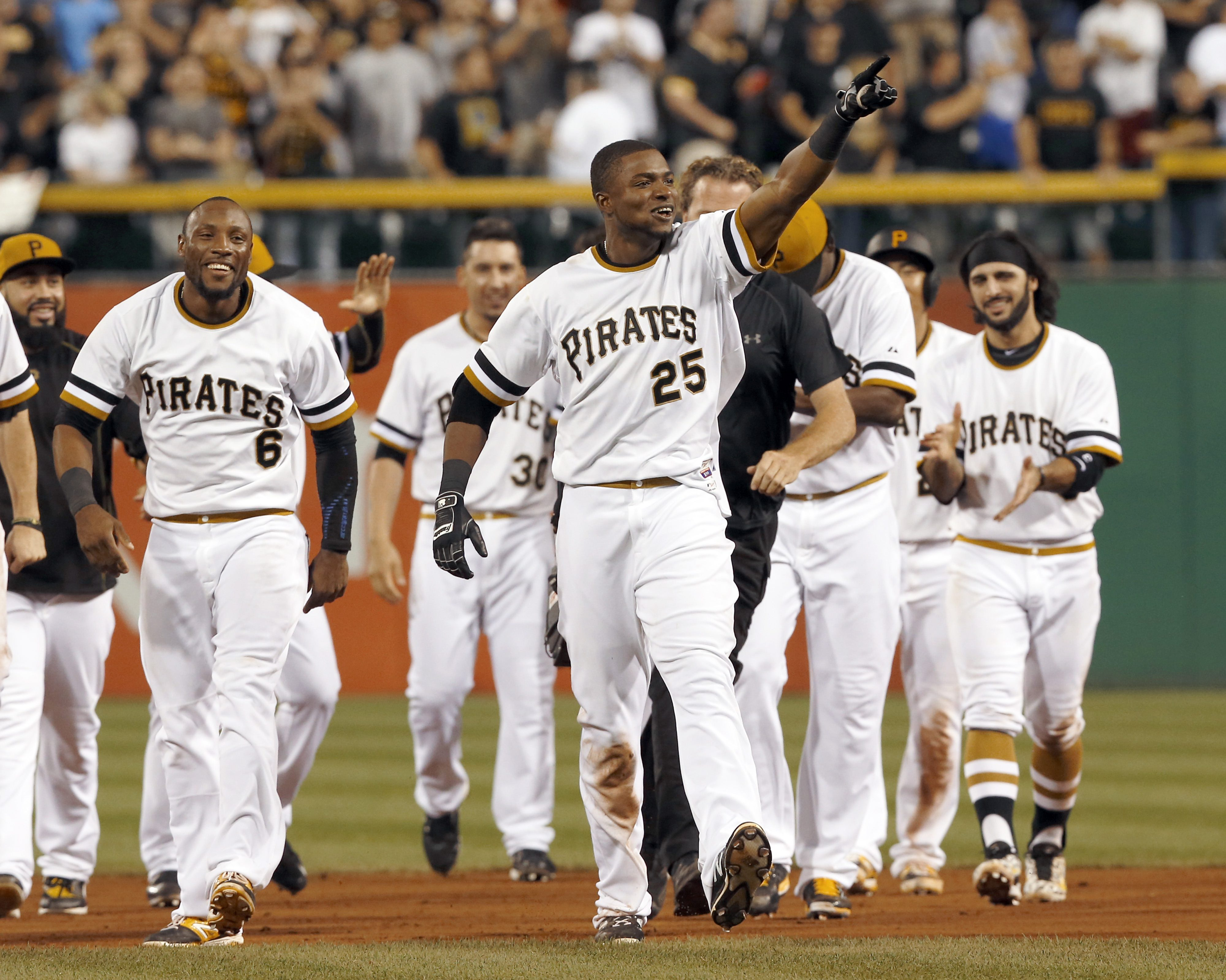 Pittsburgh Pirates' Gregory Polanco (25) points to the stands as he leaves the field while celebrating with teammates after driving in the winning run to defeat the St. Louis Cardinals in the tenth inning of a baseball game, Sunday, July 12, 2015, in Pittsburgh. The Pirates won 6-5 in 10 innings. (AP Photo/Keith Srakocic)
