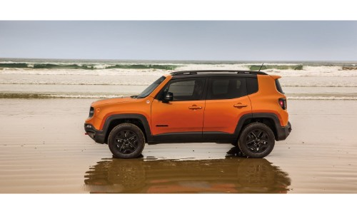 2018 Jeep Renegade exterior side shot orange paint job parked on a wet shallow beach
