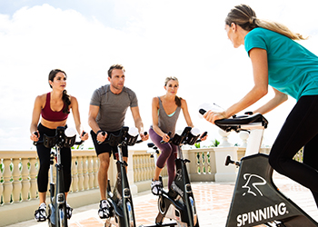 Three guests enjoy a cycling class on the Ocean Fitness center terrace