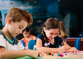 Two children enjoy arts and crafts activities at The Breakers Family Entertainment Center