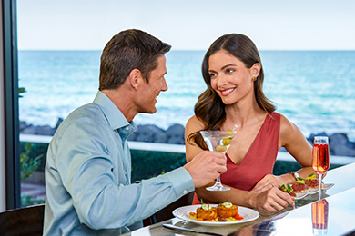 A couple enjoy food and cocktails at Seafood Bar