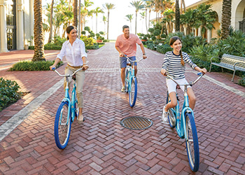 A family of three enjoys a bike ride at The Breakers
