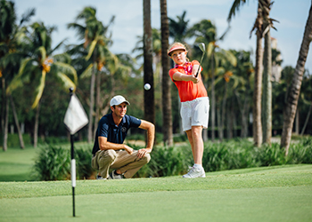 A junior golfer receives private instruction at the John Webster Golf Academy
