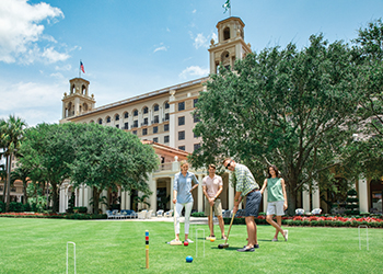 A family of four enjoys a game of croquet on the Front Lawn at The Breakers