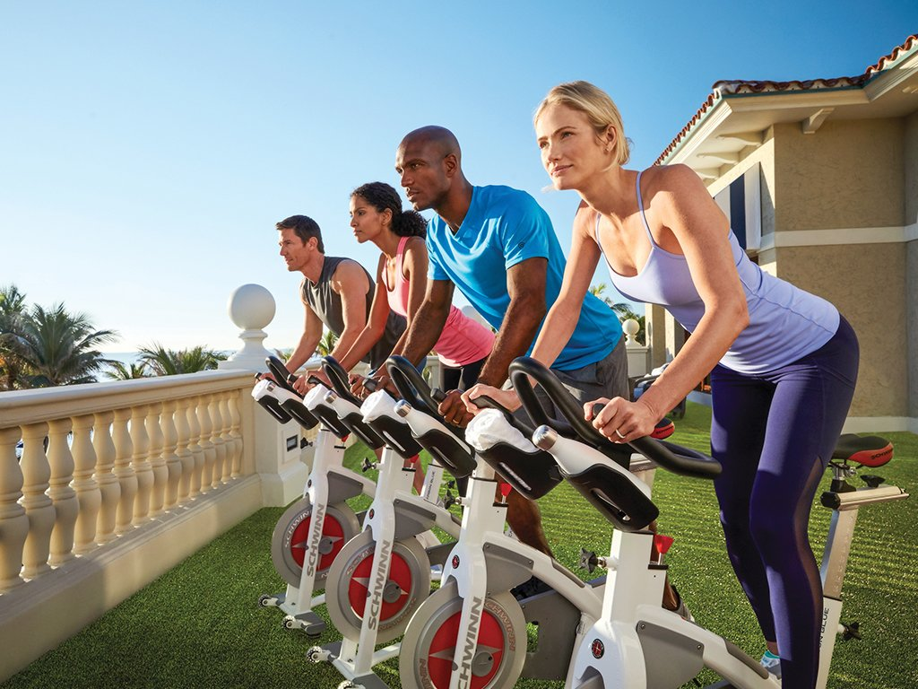 Four guests enjoy a cycling class on the Ocean Fitness center terrace