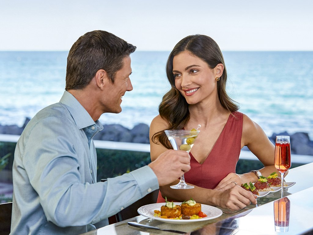 A couple enjoy food and cocktails at Seafood Bar at The Breakers