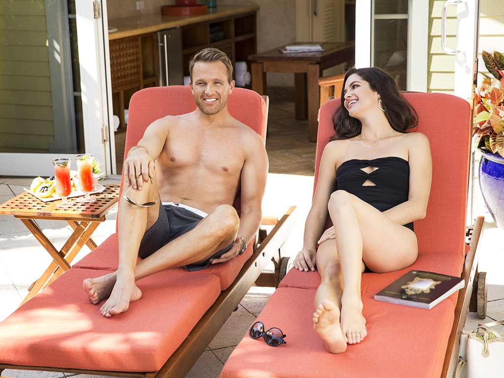 A couple relax on lounge chairs at their private, poolside bungalow at The Breakers Beach Club